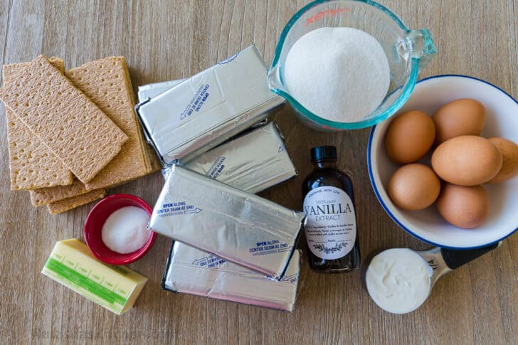 Ingredients for cheesecake with cream cheese, eggs, sour cream, sugar, vanilla, graham crackers and butter