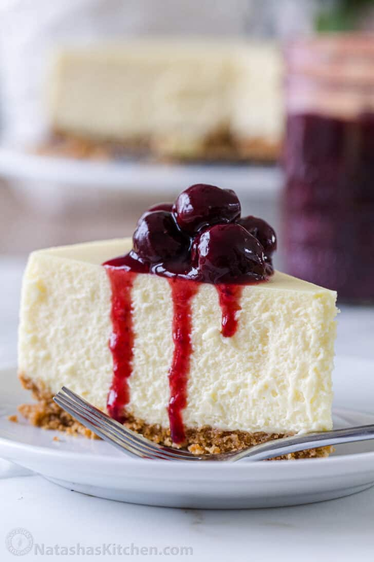 Cheesecake slice on a plate with a fork and cherry topping
