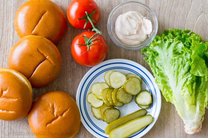 Toppings for chicken sandwiches with buns, tomatoes, lettuce, pickles, and mayo