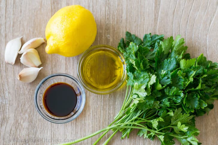 Chimichurri sauce ingredients with parsley, fresh lemon, extra virgin olive oil, soy sauce and garlic cloves