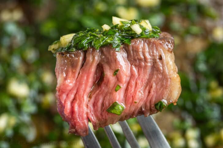 Juicy bite of steak on a fork topped with chimichurri sauce
