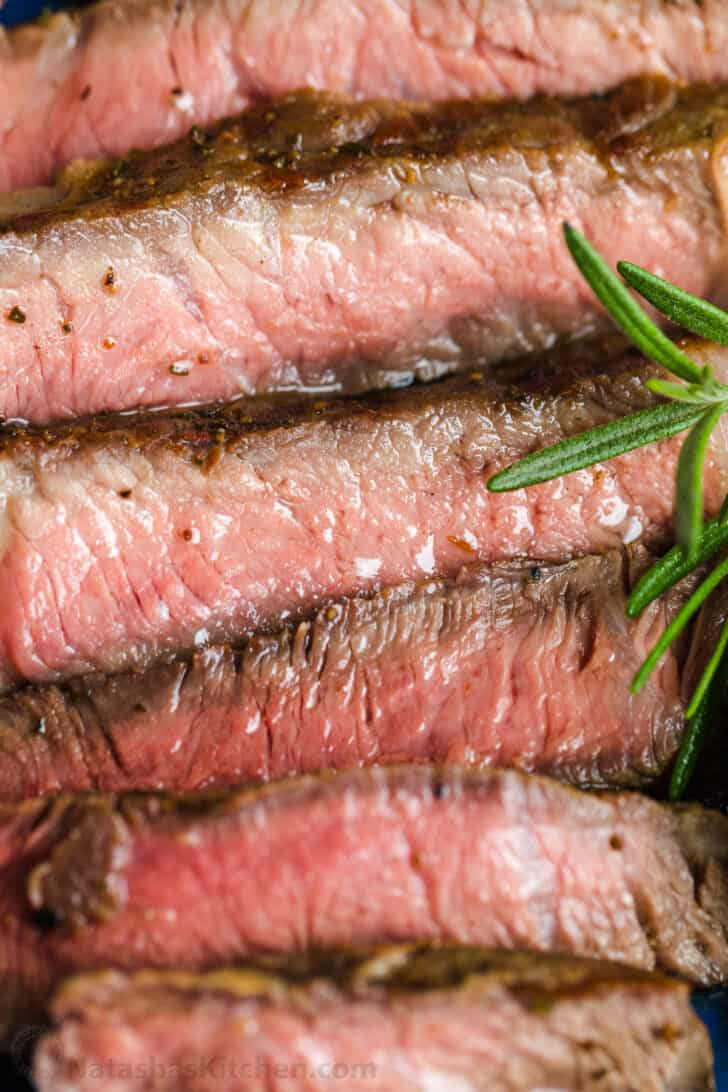 Sliced grilled steak on a platter with rosemary