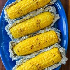Grilled Corn in Foil on a blue platter