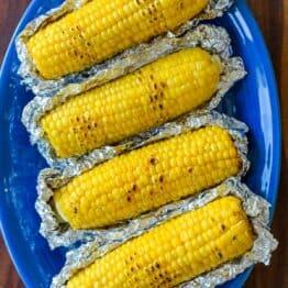 Grilled Corn in Foil on a blue platter
