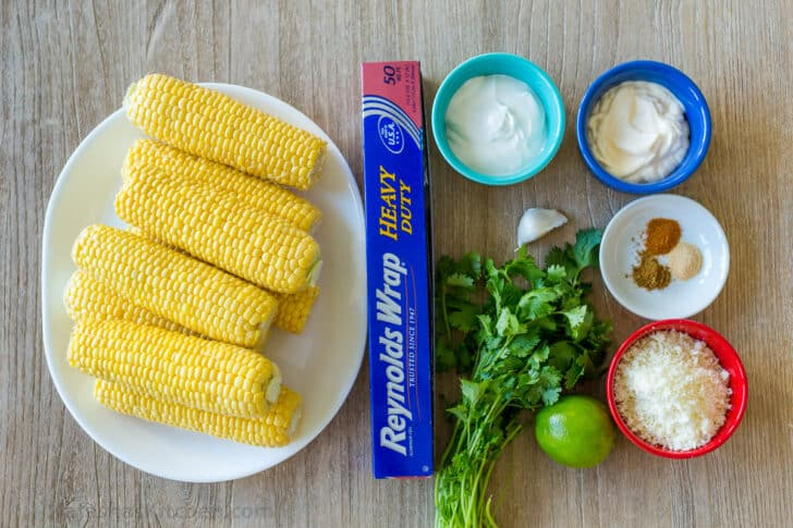 elote ingredients with corn, sour cream, mayo, cotija cheese, lime, cilantro, garlic and spices