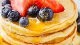 Ricotta Pancakes stacked on plate with fruit and drizzled with maple syrup
