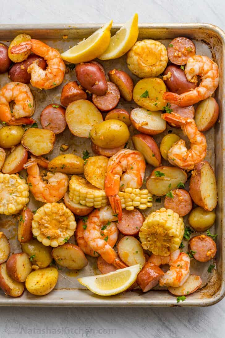 Shrimp boil baked and served on a baking sheet with sausage, corn, shrimp, and potatoes