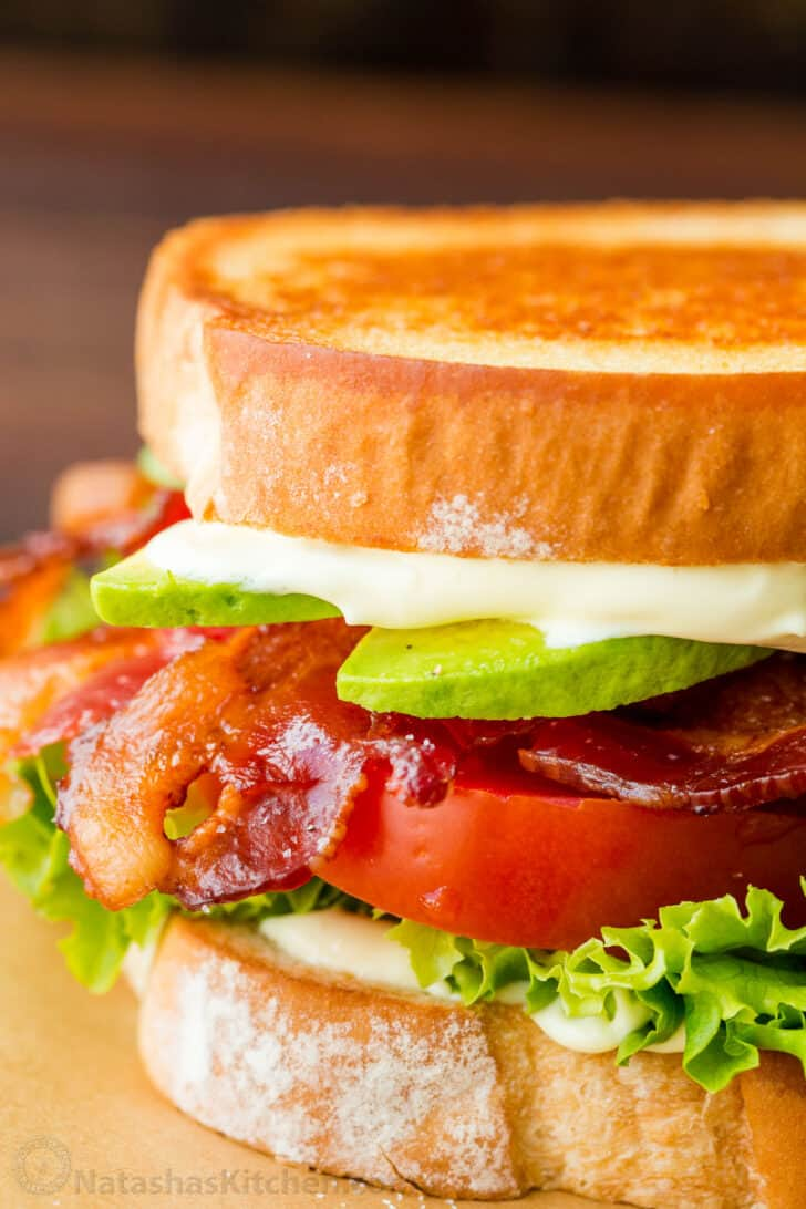 Fully assembled BLT Sandwich with bacon, lettuce, tomato, avocado and sauce