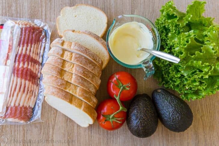 Ingredients for BLT sandwich with bacon, bread, tomatoes, lettuce, avocados and sandwich spread