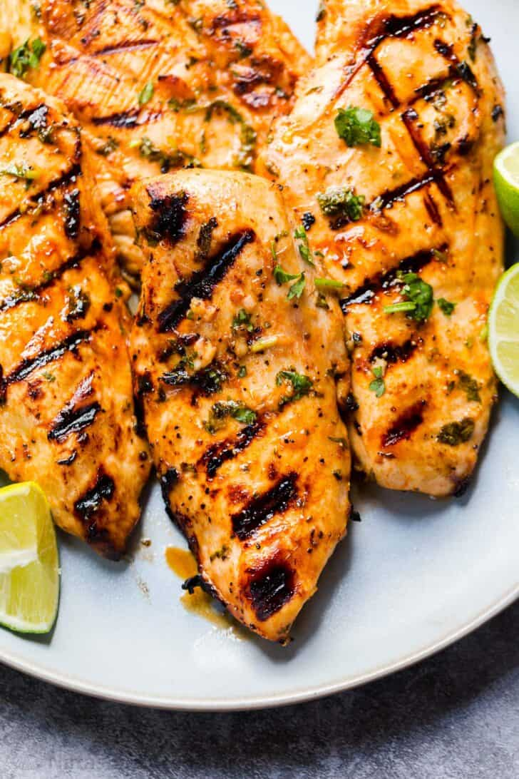 Grilled chicken breasts on a plate with lime.
