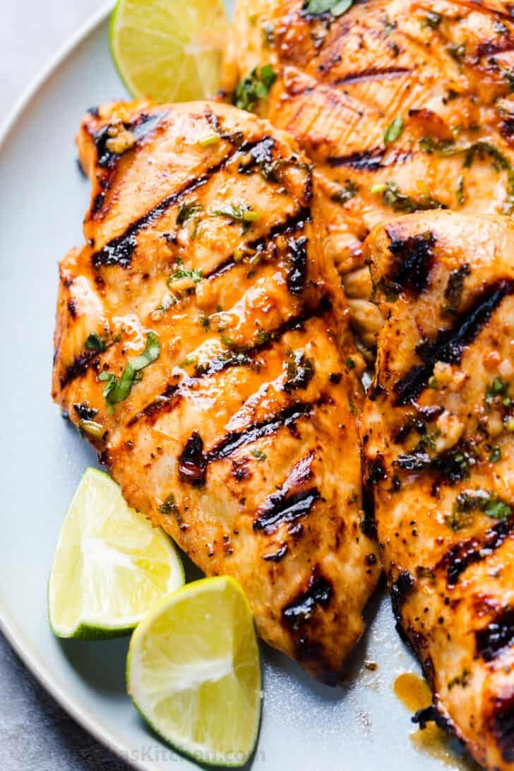 Grilled chicken breasts on a plate with lime pieces.