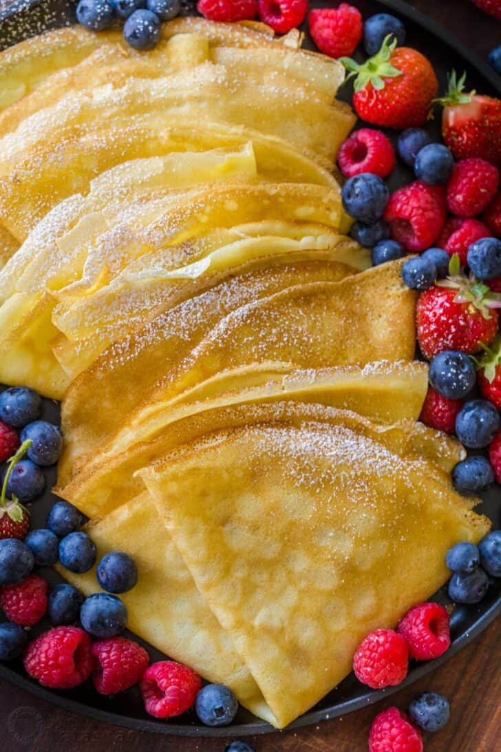 Crepe recipe dusted with powdered sugar and surrounded by berries.