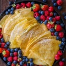 Crepes arranged on a skillet and dusted with powdered sugar