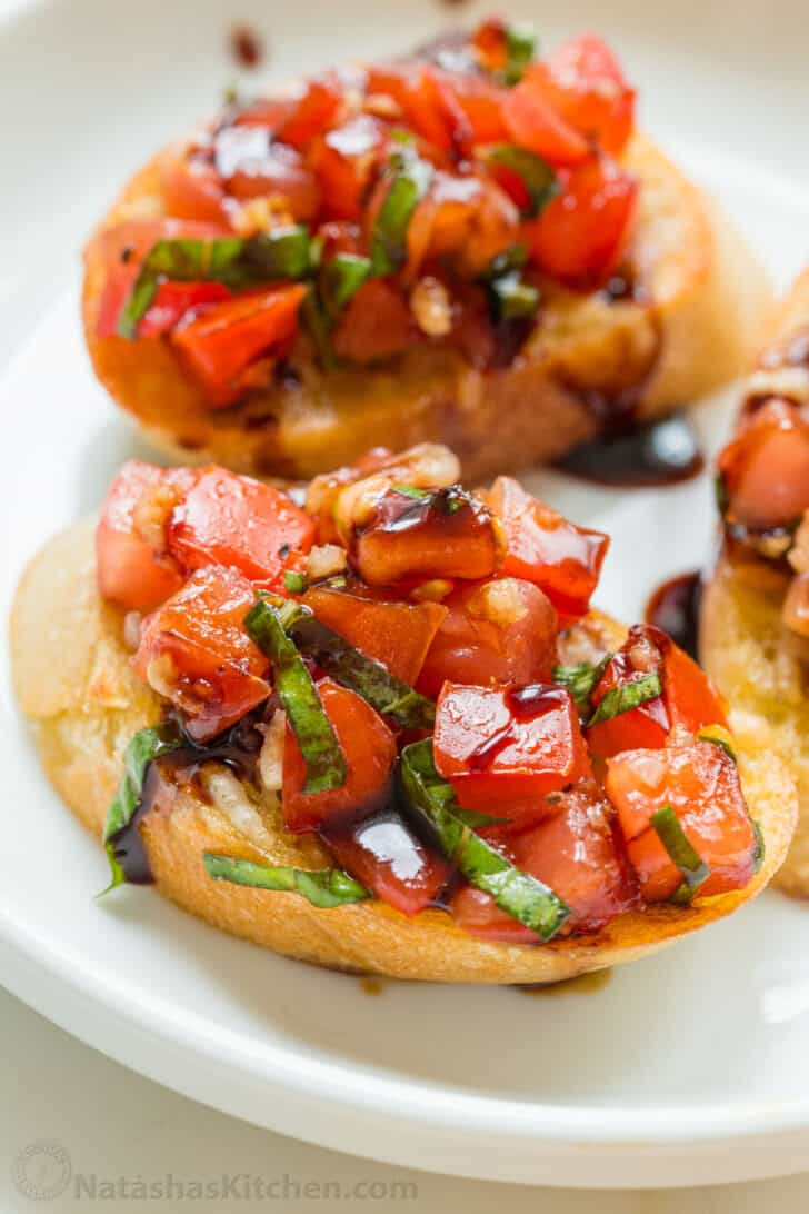 Up close bruschetta topped with tomatoes and basil