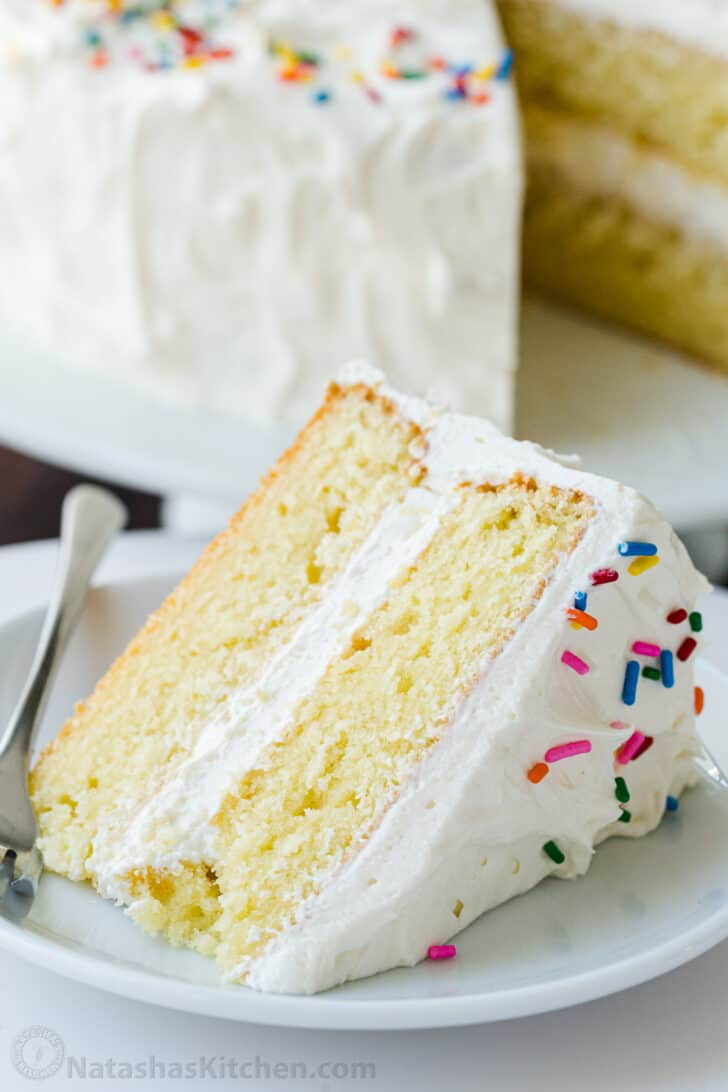 Vanilla cake with buttercream frosting on a plate with fork