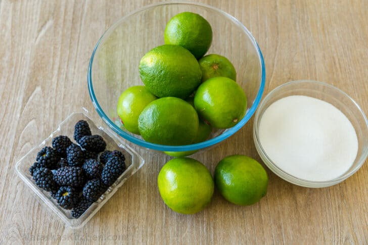 Fresh limes, blackberries and sugar to make limeade