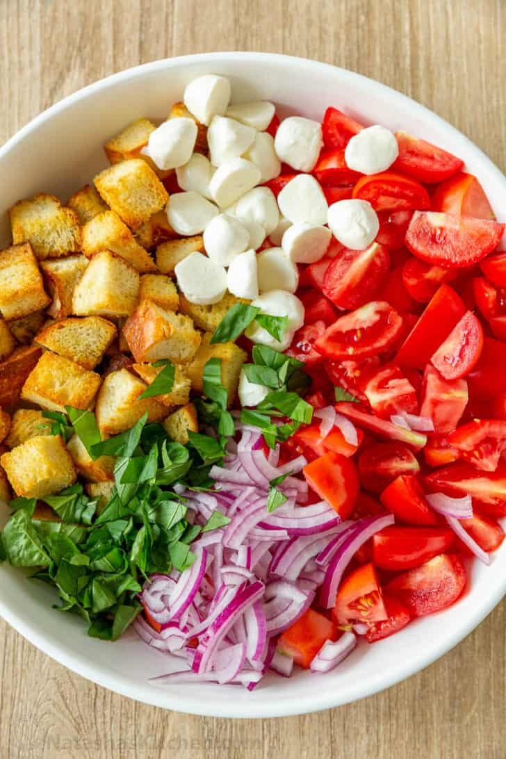 Panzanella Salad ingredients arranged in bowl with toasted bread, tomatoes, basil, onion and cheese