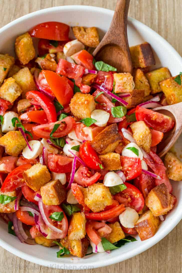 Panzanella Salad tossed in a bowl garnished with basil