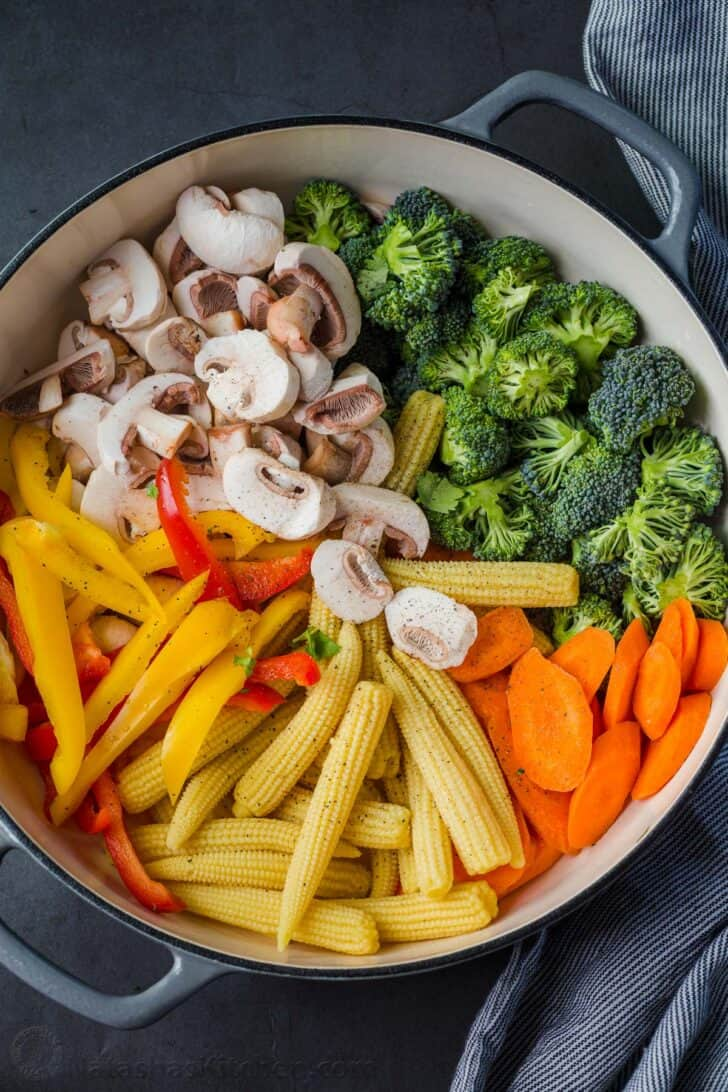 Vegetables cut and prepper in a skillet for stir fry recipe with a towel on the side of the skillet.