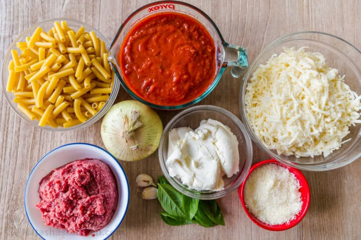 Ingredients for baked ziti with ziti pasta, marinara, ground beef, mozzarella, ricotta and parmesan cheese