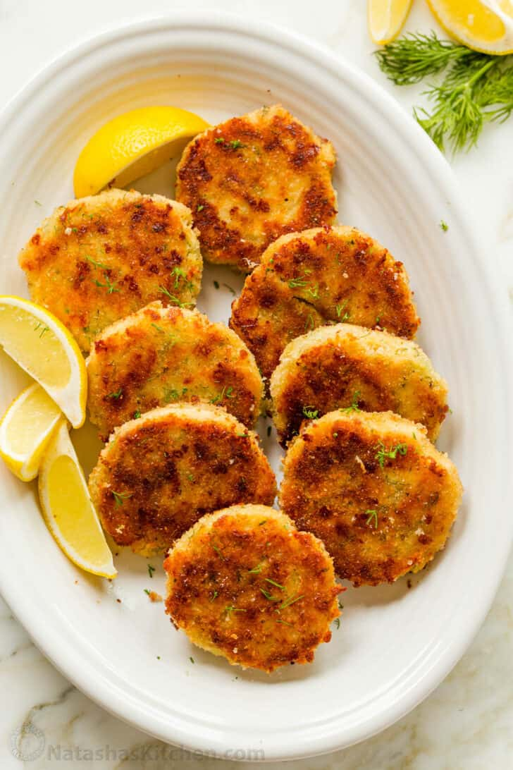 Chicken patties on a platter with lemon wedges