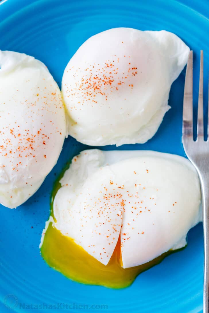 Perfectly cooked poached eggs on a plate with fork