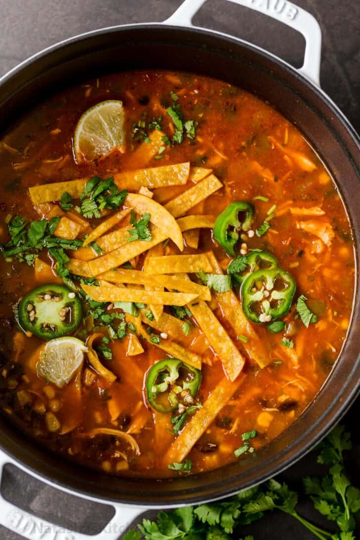 Easy chicken tortilla soup in pot garnished with tortilla strips, jalapeños and cilantro
