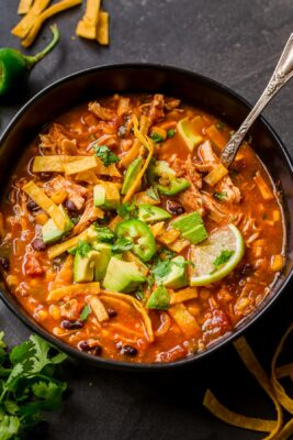 chicken Tortilla Soup garnished with avocado, cilantro and lime