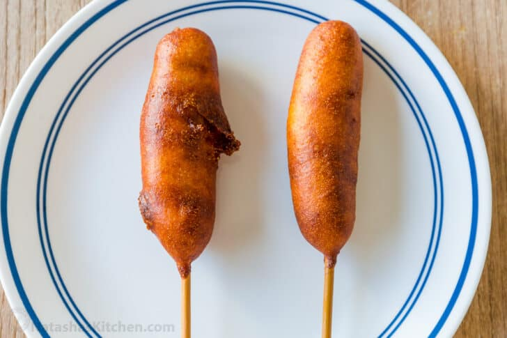 a cracked corn dog next to a perfect corn dog