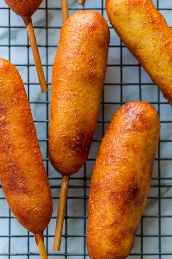 corn dogs cooling on a wire rack