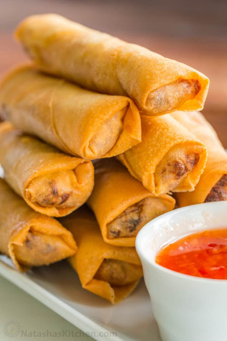 A plate of egg rolls stacked on top of each other with bowl of dipping sauce