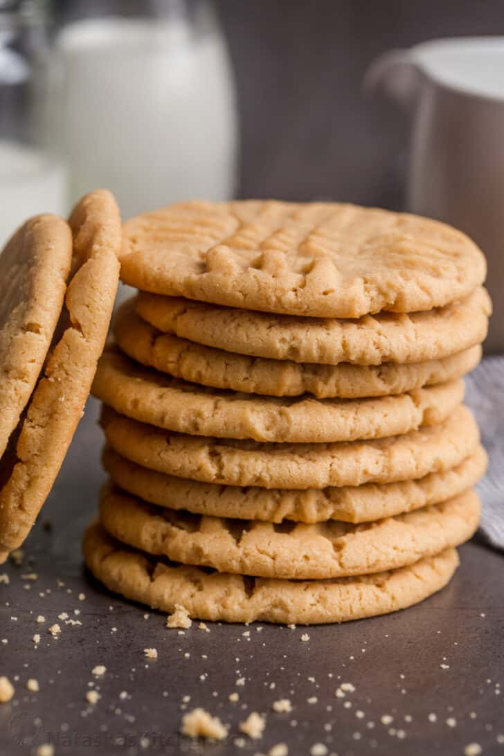 Peanut butter cookies stacked with milk in glass cups.