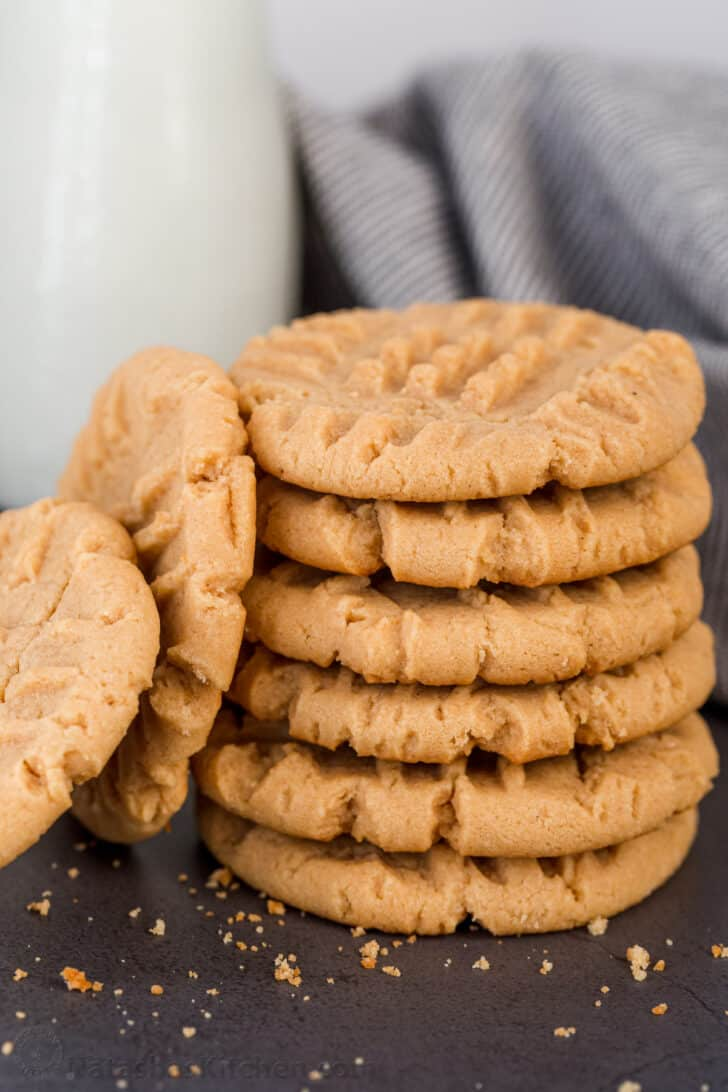 Cookies stacked with a glass of milk on the side.