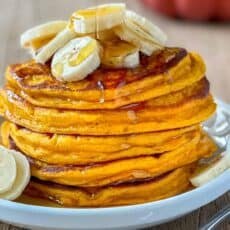 Pumpkin pancakes stacked on a plate