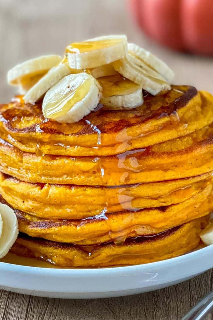 Stack of pumpkin pancakes topped with banana and maple syrup