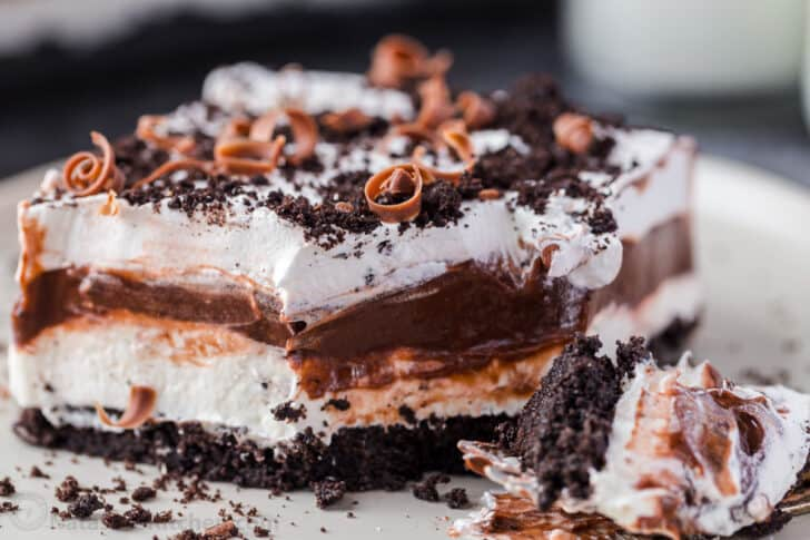 A slice of chocolate lasagna cake on a white plate topped with chocolate shavings.
