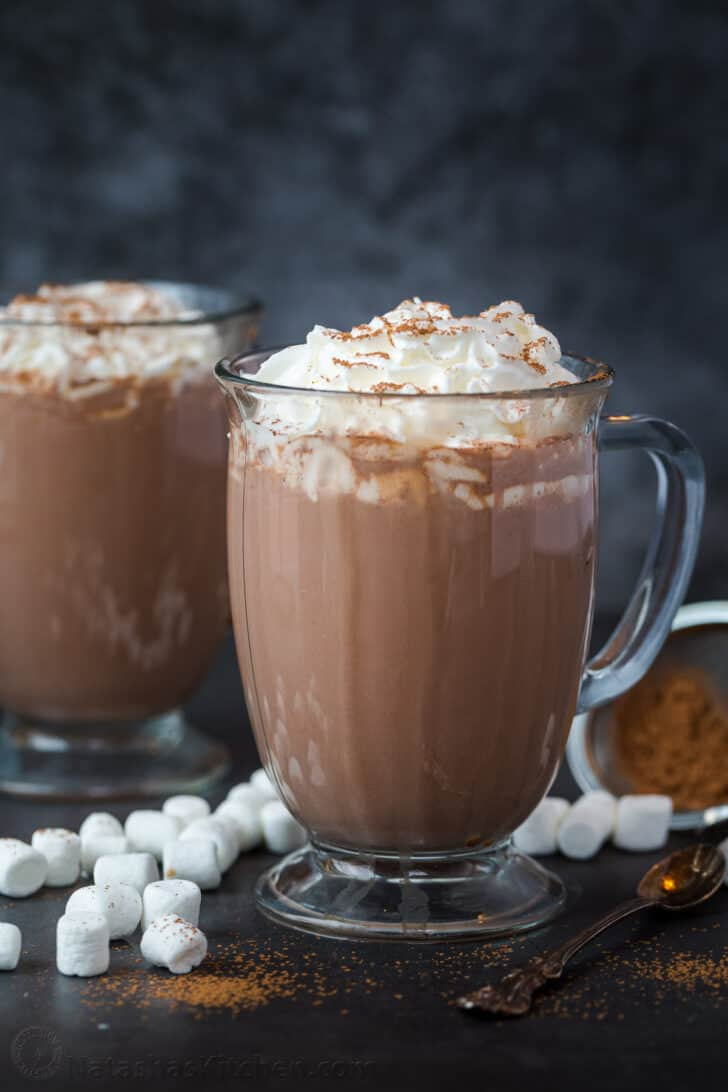 A cup of hot chocolate topped with whipped cream and cocoa powder next to another cup and marshmallows.
