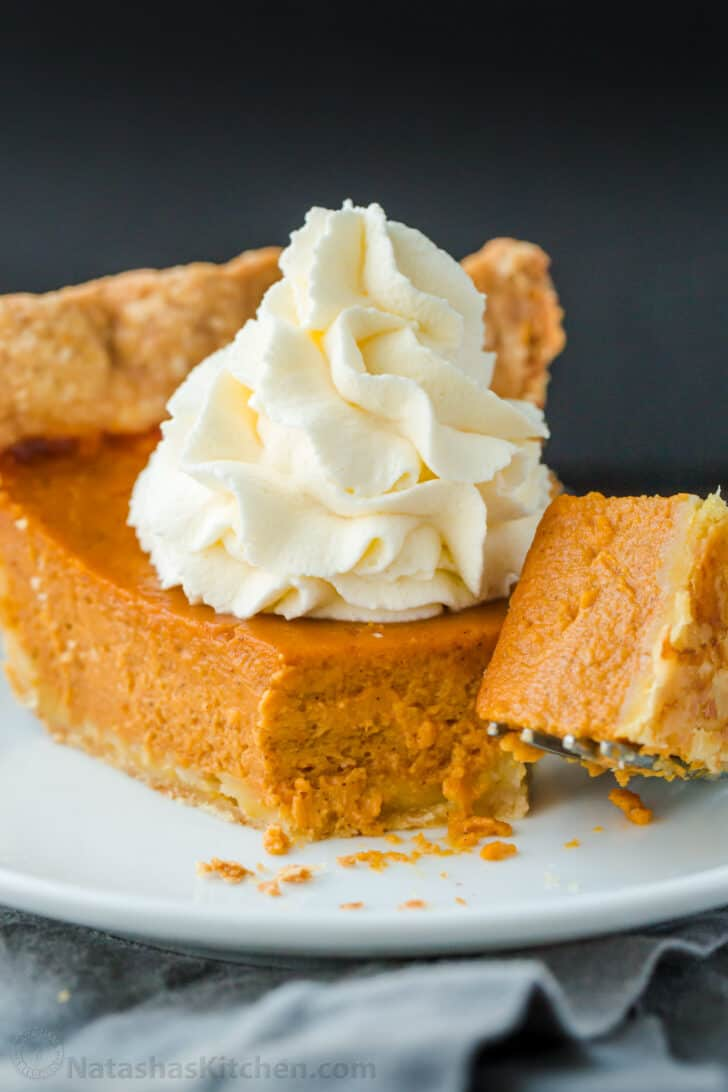 Classic Pumpkin pie served on a plate with whipped cream