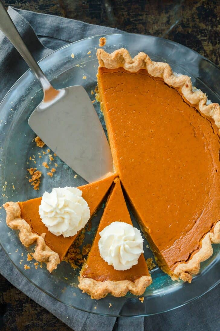 Homemade pumpkin pie slices topped with whipped cream