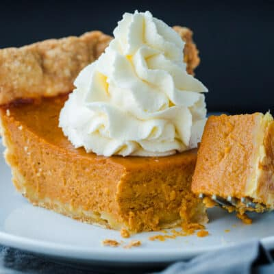pumpkin pie on a plate with whipped cream