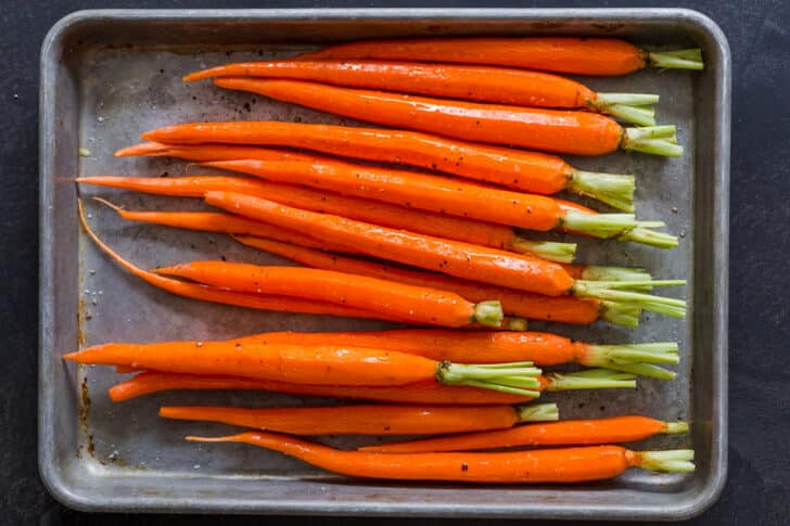 Carrots on a baking pan ready to be roasted.