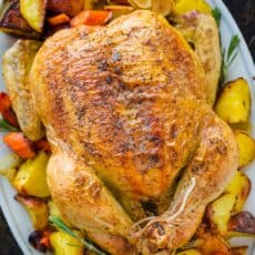 Whole Roast Chicken on a platter with vegetables