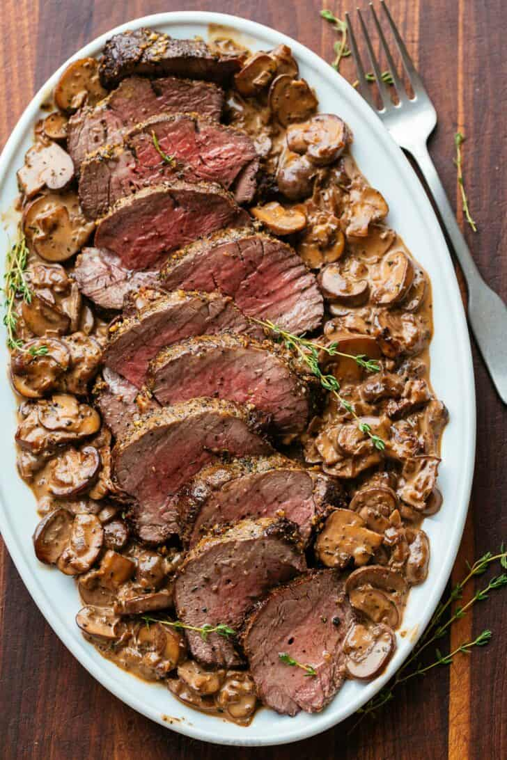 Sliced beef tenderloin with mushrooms on serving platter with thyme