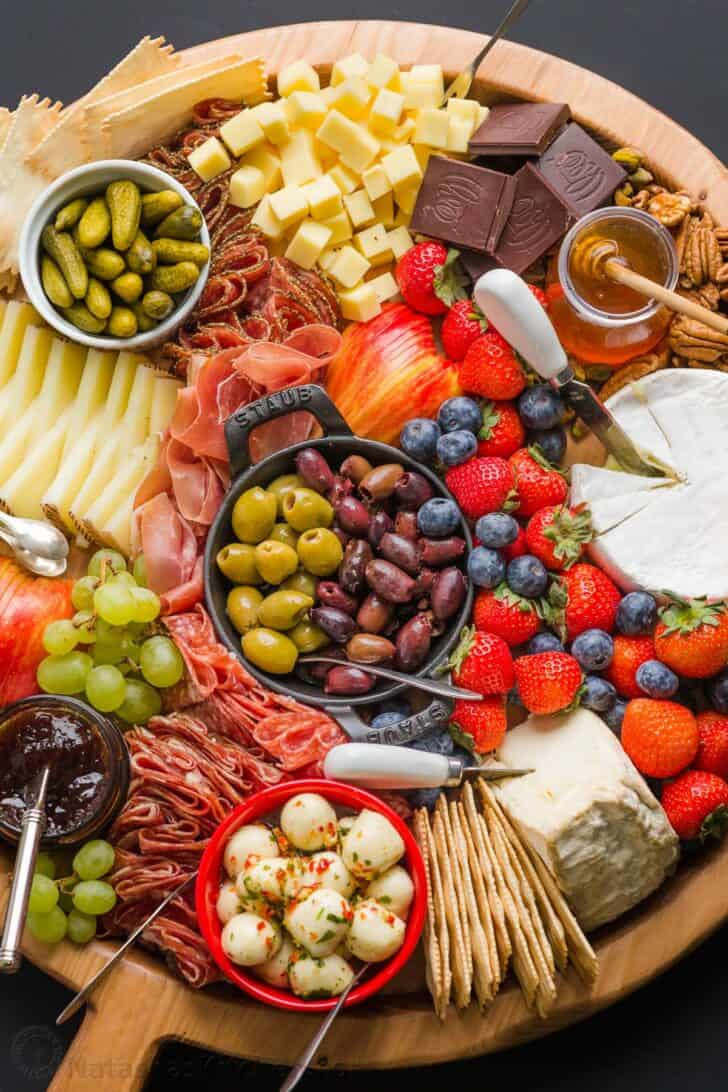 how to build a charcuterie board with cheeses, meats, condiments, pickled ingredients, fruit and nuts