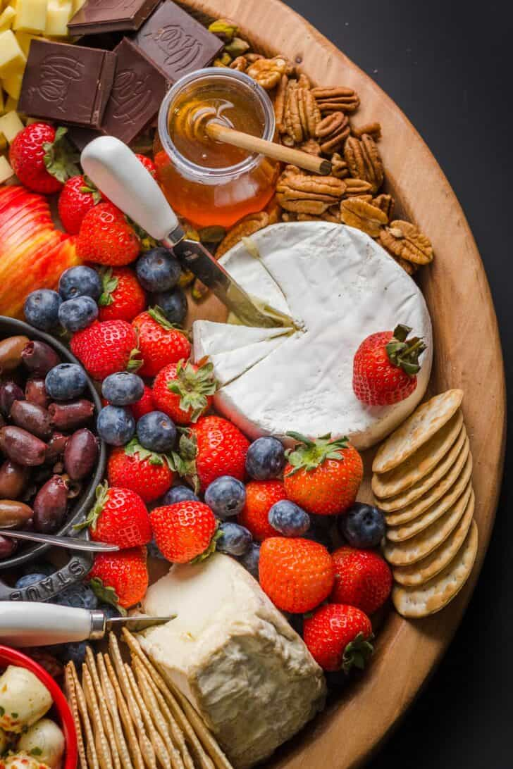 Cheese, fruit, nuts, and condiments arranged on a charcuterie board