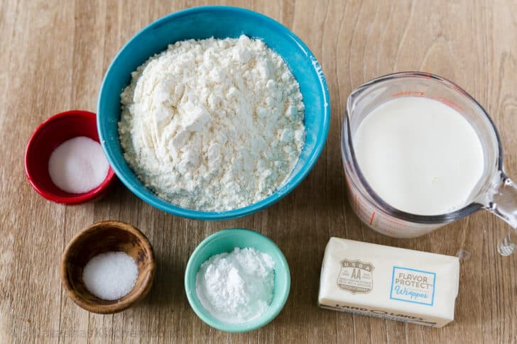 Ingredients to make biscuits with butter, flour, half and half, baking powder, salt and sugar
