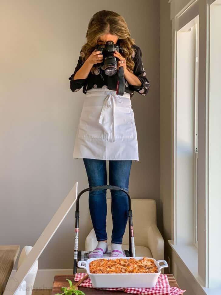 Natasha on ladder photographing food