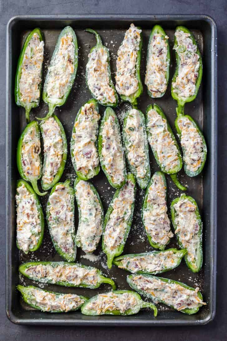 Uncooked stuffed jalapeno poppers in a baking sheet topped with parmesan cheese.
