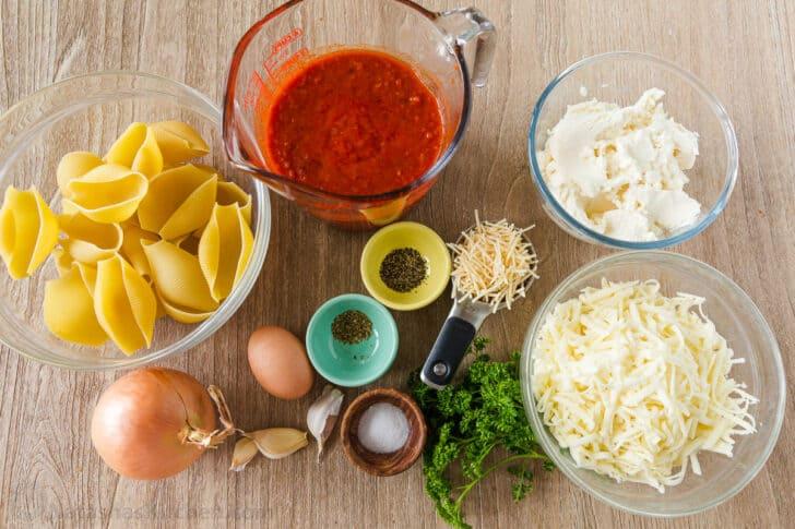 Recipe ingredients with jumbo shells, cheese, marinara, onion and garlic
