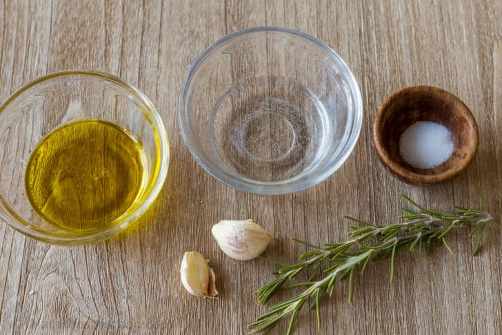 Ingredients for focaccia topping with oil, water, salt, garlic and rosemary